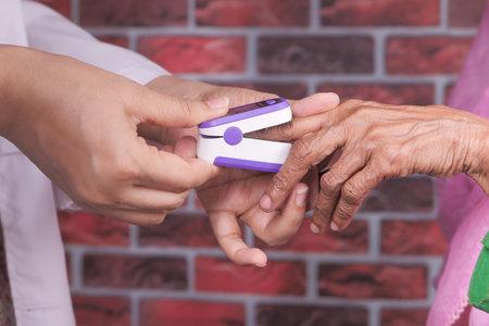 senior women hand using pulse oximeter
