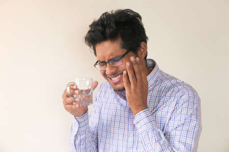 young man with sensitive teeth and glass of cold water .