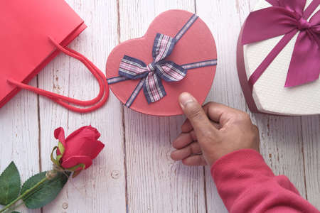 top view of mans hand holding a gift box on table