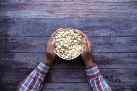 top view of mans hand holding a bowl of popcorn 스톡 콘텐츠