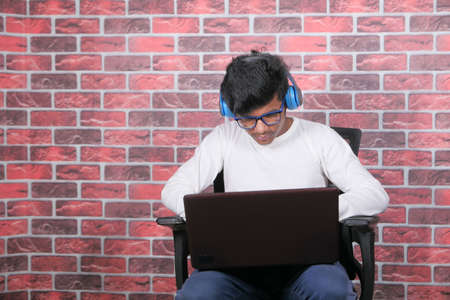 Work from home concept, young man with headphone typing on laptop 스톡 콘텐츠