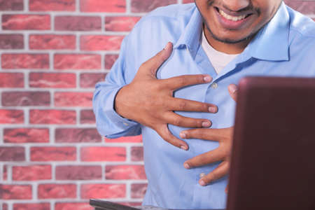business man suffering pain in heart and holding chest with hand