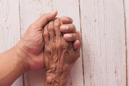 detail of mans hand hand holding senior womens hand 스톡 콘텐츠
