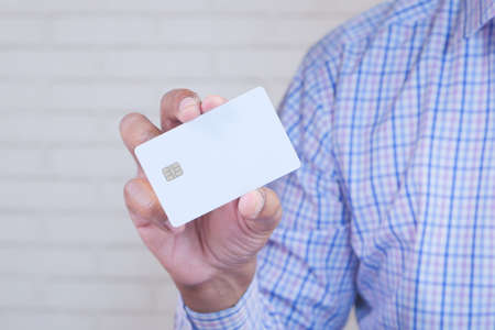 Man in casual dress showing credit card