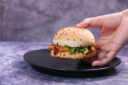 hand holding beef burger on table close up 스톡 콘텐츠