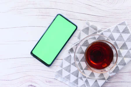 top view of smart phone and tea on table