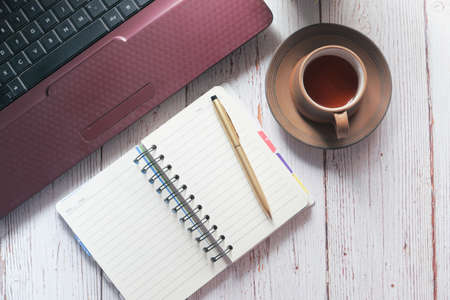 high angle view of open notepad , laptop and tea on wooden background 스톡 콘텐츠