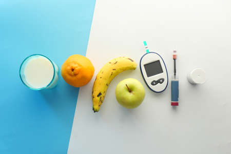 diabetic measurement tools,, fruits and milk on color background