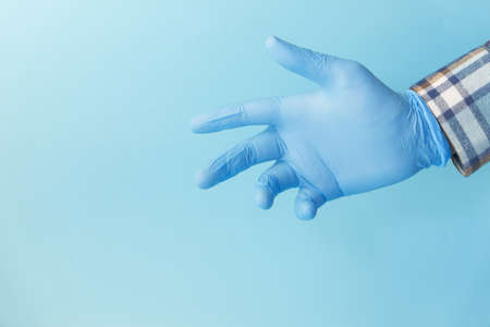 Doctor hand with glove on blue background.