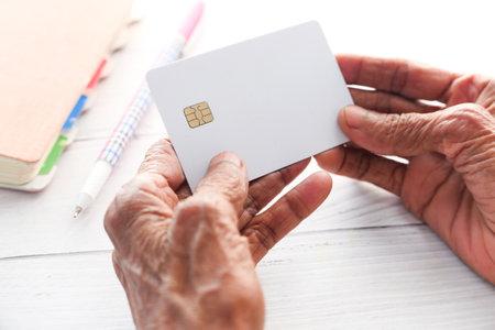 senior women hand holding credit cards reading information 스톡 콘텐츠