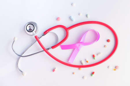 pink ribbon, pills and stethoscope on white background.