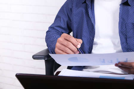 young man sitting on a chair analyzing financial data on paper