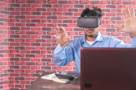 young man wearing virtual reality headset with laptop on office desk