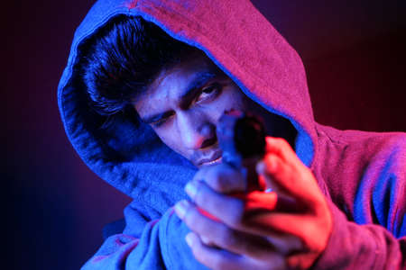 hooded man hand holding gun isolated on black 스톡 콘텐츠
