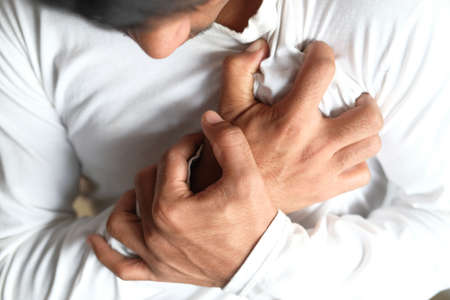 the concept of heart attack, young man suffering pain in heart