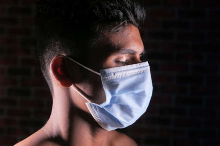 side view of man closed his eye with protective face mask isolated on black 스톡 콘텐츠