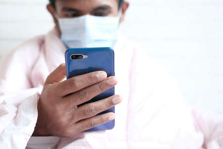 sick man in surgical face mask using smart phone, selective focus