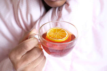 unrecognized sick man drinking lemon tea close up