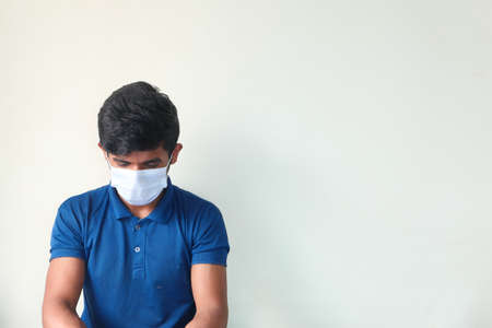 A young man with protective mask against a wall