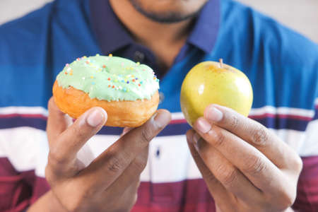 hand holding donuts and apple on hand on weight scale .