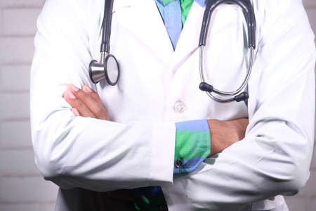 close up of doctor with arms crossed and stethoscope on neck ,