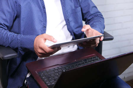 unrecognized man working from home sitting on chair using digital tablet