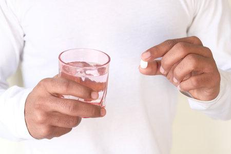 unrecognized man in white shirt taking medicine