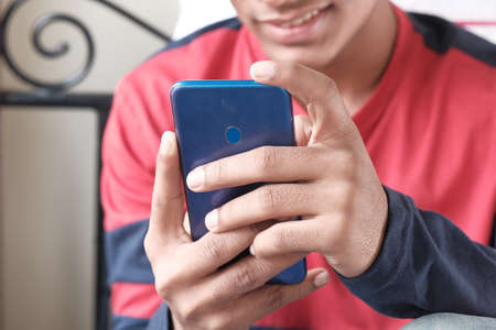 unrecognized young man sitting on bed using smart phone.
