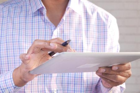 unrecognized businessman using digital tablet on office desk 스톡 콘텐츠