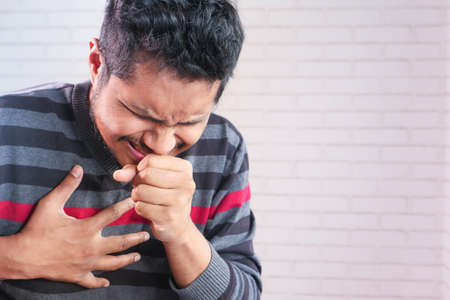 young asian man coughing and sneezes close up 스톡 콘텐츠