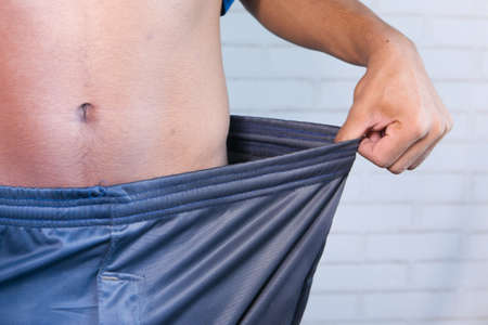 the concept of weight loss, young man pulling pant