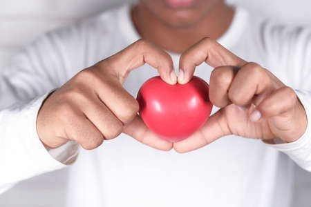 hand holding red heart symbol on white background . Stockfoto