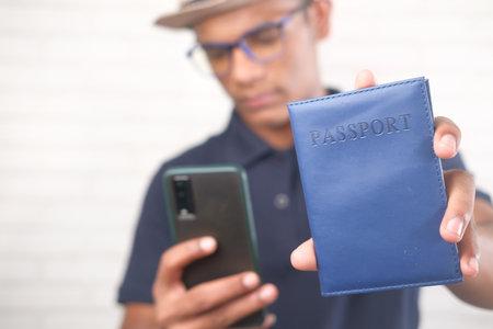 a traveler holding a passport and smart phone