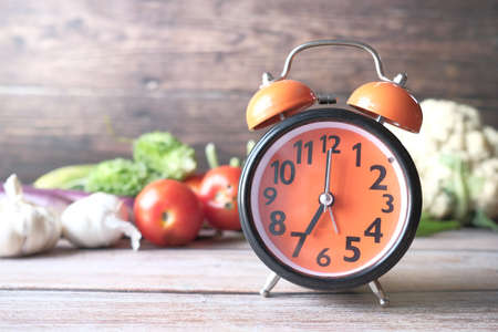 alarm clock and fresh vegetables on table with copy space