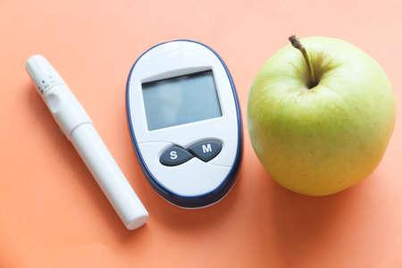 diabetic measurement tools, apple on orange background