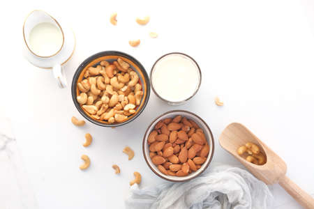 almond , cashew nut in glass bowl and milk on white background Imagens