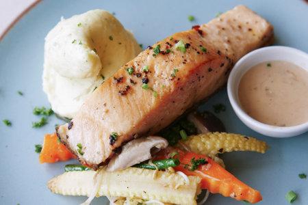 tasty salmon, mash potato and vegetable on plate Фото со стока