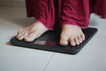 womans feet on weight scale close up.