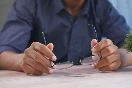 Close up of man hand holding old eyeglass