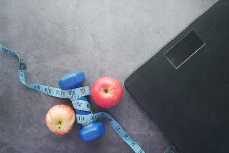 Fitness concept with dumbbell, apple and weight scale on black