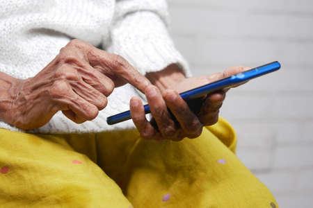 senior women hand using smart phone close up Фото со стока