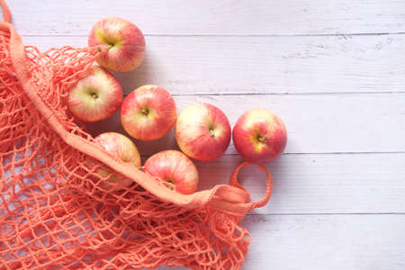 fresh apple in a shopping bag on wooden table