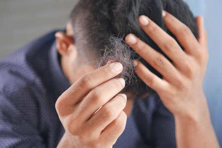 man hold his list hair close up Фото со стока