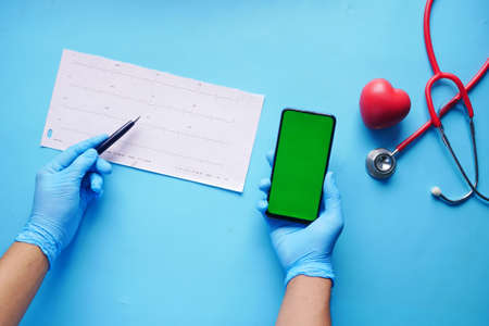 doctor hand in medical gloves analyzing cardio diagram and holding smart phone