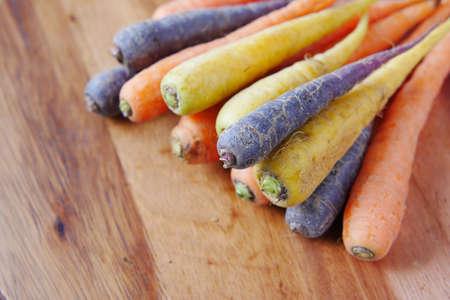 mixed colorful carrot on a chopping board Фото со стока