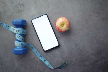 smart phone , dumbbell and apple on black background