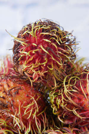 stack of rambutan in a chopping board on table