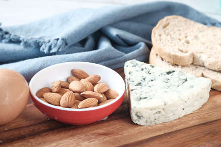 cheese, milk , brown bread and almond nut on table.