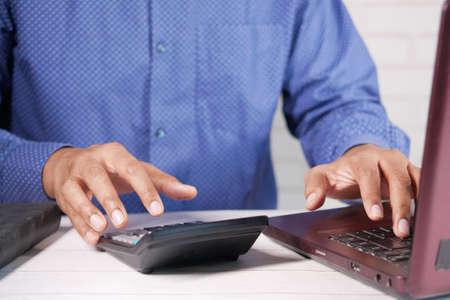 Close up of man hand using calculator Фото со стока