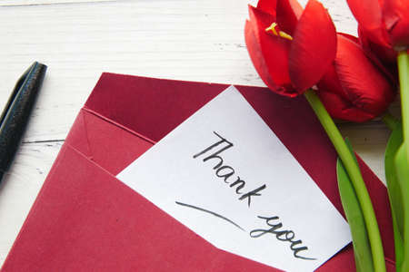 thank you message and envelope on wooden table Standard-Bild